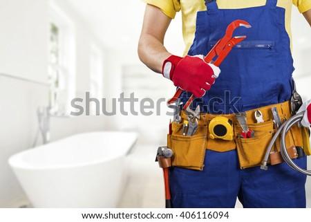 plumber with tool belt standing in bathroom