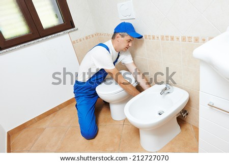 plumber worker working with spanner at sanitary washbasin installation system - stock photo