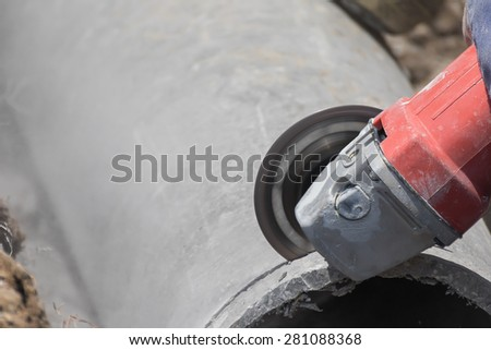 Plumbers cutting concrete water pipes by metal grinding - stock photo