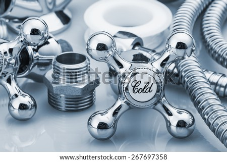plumbing and tools in a light background. focus on the word cold. toning image - stock photo