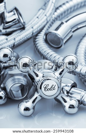 """plumbing and tools on a light background. Focus on the word """"cold"""". toned image - stock photo"""
