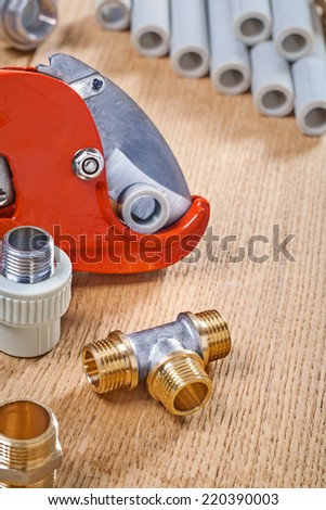 plumbing fixtures and pipe cutter with pipes on wooden board