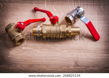 Plumbing Tools Composition Of Brass Pipe Connectors On Wooden Board  - stock photo