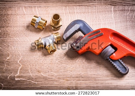 Plumbing Tools Composition Of Brass Pipe Connectors On Wooden Board and Monkey Wrench