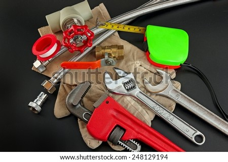 Plumbing tools on black background. - stock photo