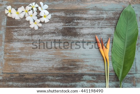 plumeria and bird of paradise flower with vintage wood background, flat lay image, copy space  - stock photo