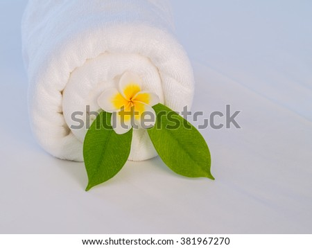 Plumeria flower and leaf in folded white towel on bed in spa - stock photo