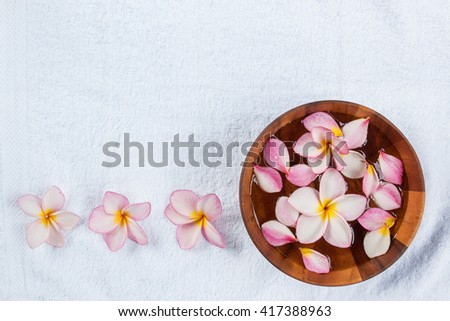 Plumeria flower in a bowl of water on white towel.