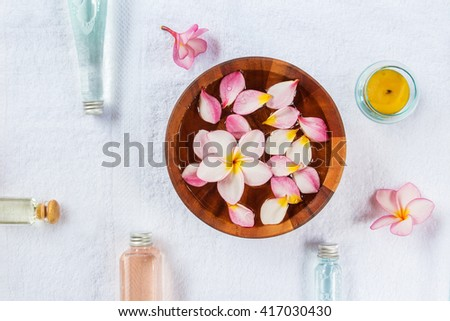 Plumeria flower in a bowl of water on white towel with spa treatments.