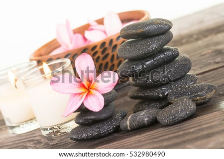 Plumeria flowers and black stones close up