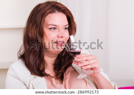 Plump and elegant woman tests a glass of red wine