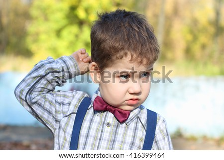 Plump little boy in shirt and bow tie thinks and scratches his head in sunny park - stock photo