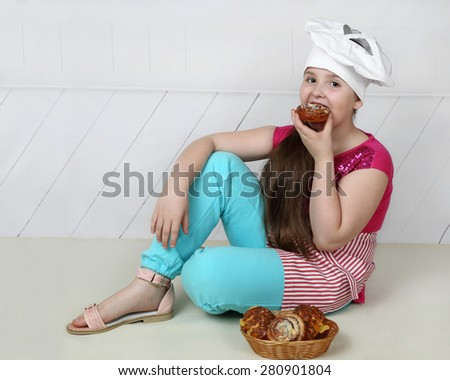 Plump little girl in chief hat sits on floor and eats pastry - stock photo