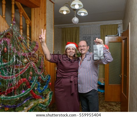 Plump smiling mature woman and aged bald man are posing near Christmas tree in home interior with wooden staircase.