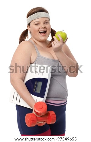 Plump woman biting green apple, holding dumbbells and scale, dieting, smiling. - stock photo