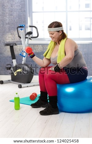 Plump woman exercising with dumbbells at the gym. - stock photo