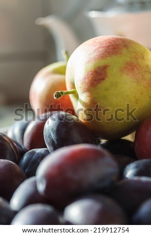 Plums and apples - autumnal fruits on the kitchen table - stock photo