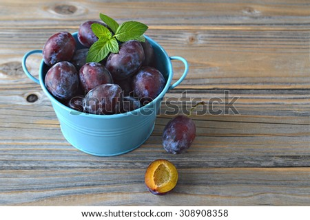 Plums and mint leaves in the bowl on wooden background - stock photo