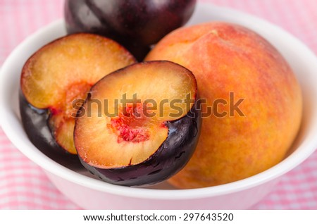 Plums and Peaches in white bowl on pink background.  Closeup with selective focus and shallow depth of field. - stock photo