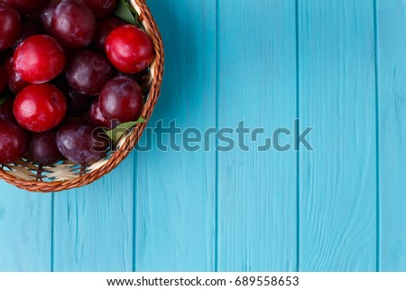 Plums In Basket On Light Blue Table. Freshness, Harvest, Fruits Concept.  Free