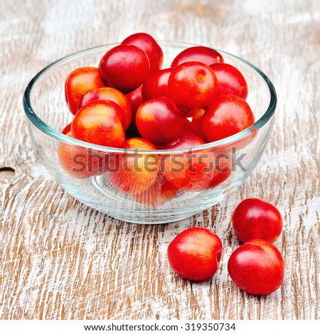 Plums in glass bowl on a rustic table. Square image