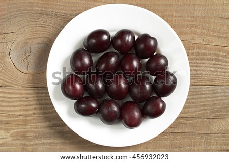 Plums in plate on wooden background, top view
