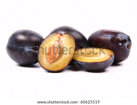 Plums on white background - one cut in half with a pit visible - stock photo