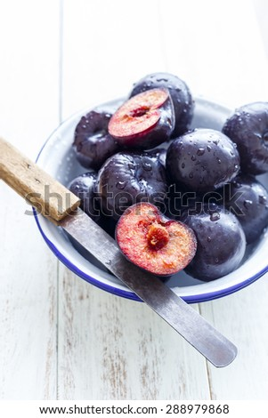 Plums Sliced and Whole plums in a blue rimmed white bowl on a white rustic background  - stock photo
