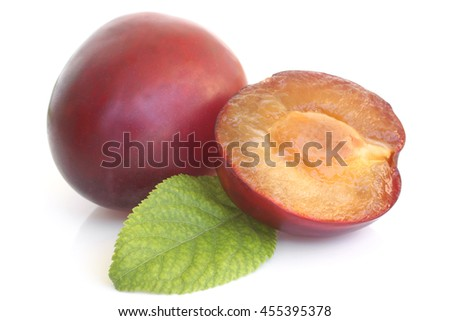 Plums with green leaf on white background    - stock photo