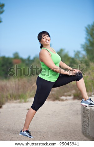 Plus Size Female Exercise Stretch Outdoor Under Sunny Blue Sky - stock photo