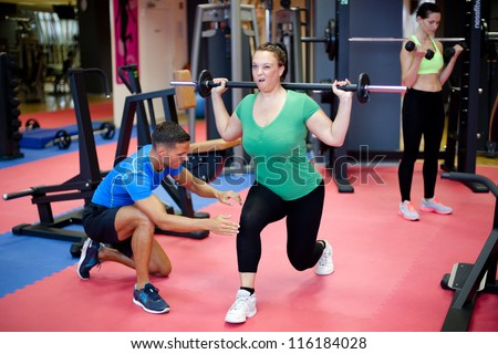 Plus size woman's first training with personal trainer - stock photo