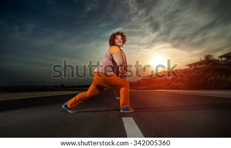 Plus size woman stretching legs for warming up before running in city park on sunset - stock photo