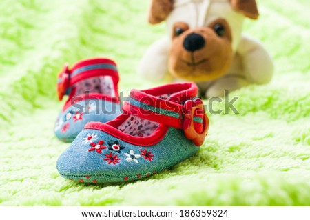 Plush puppy looking at baby shoes. - stock photo