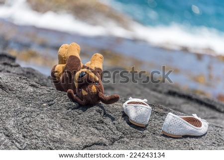 Plush toy dog and white shoes at beach - stock photo
