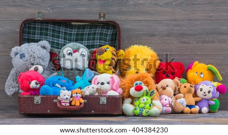 plush toys in the suitcase, wooden background - stock photo
