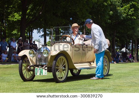 PLYMOUTH - JULY 26: A classic car owner is interviewed  July 26, 2015 at the Councors D'Elegance in Plymouth, Michigan. - stock photo