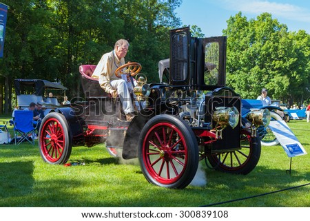 PLYMOUTH - JULY 26: A driver starts up a 1905 vintage steam engine automobile July 26, 2015 at the Councors D'Elegance in Plymouth, Michigan. - stock photo