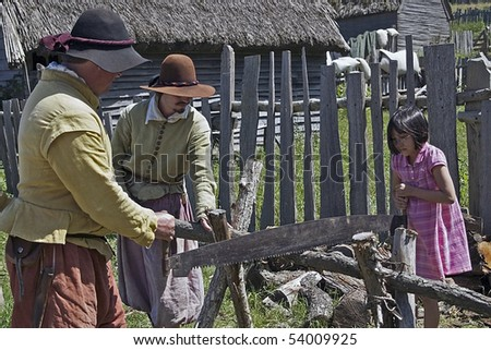 PLYMOUTH, MA - JULY 24: Male pilgrims and a little visitor saw wood at Plimoth Plantation July 24, 2009 in Plymouth, MA. The plantation features the recreation of an English village in 1627.