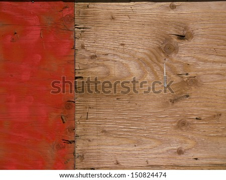 Plywood background, left third painted orange.  Grain and knots visible. - stock photo