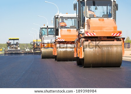 Pneumatic steam road rollers machines compacting fresh asphalt during highway construction works on tracked paver equipment background - stock photo