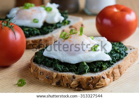 Poached egg on a piece of brown bread with spinach on a wooden table - stock photo