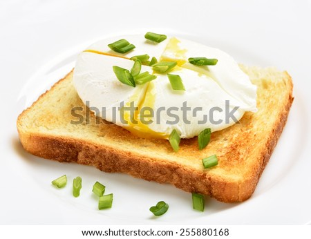 Poached egg on bread over white plate, close up view - stock photo