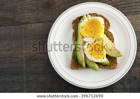 Poached egg on brown bread toast and avocado.