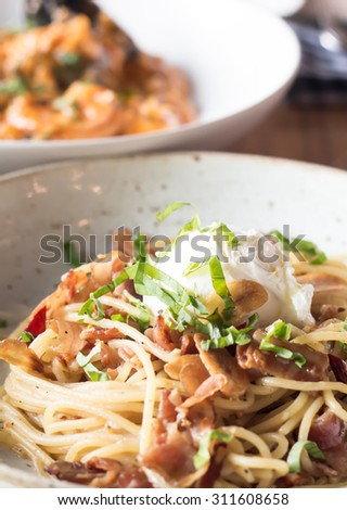Poached egg on spaghetti with bacon and garlic - stock photo