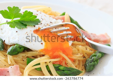 Poached egg on spaghetti with green asparagus - stock photo