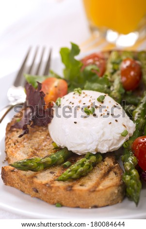 Poached egg on toasted bread with asparagus, tomatoes, greens and served with fresh orange juice - stock photo