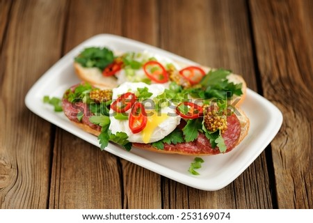 Poached egg sandwiches with chili, scallion and salami selective focus - stock photo