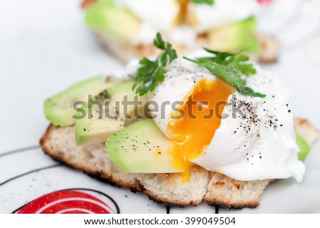 Poached egg with avocado on white bread. Close up.
