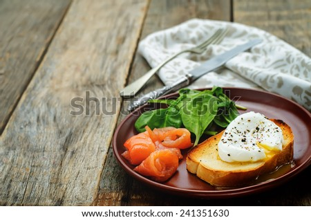 poached egg with salmon and spinach on a dark wood background. tinting. selective focus - stock photo