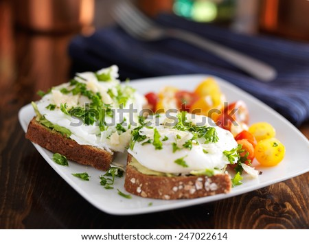 poached eggs and avocado on toast with tomatoes - stock photo